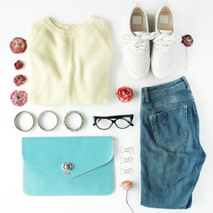 flat lay feminini clothes and accessories collage with cardigan, jeans, glasses, bracelet, clutch, shoes and dry roses on white background.