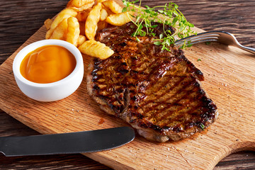 Grilled Beef Steak with Chips and Mango souce on wooden board.