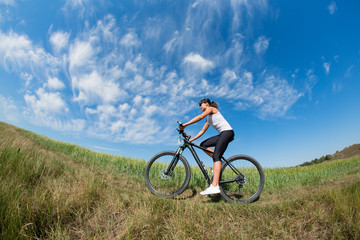 Sport bike woman on the meadow with a beautiful landscape