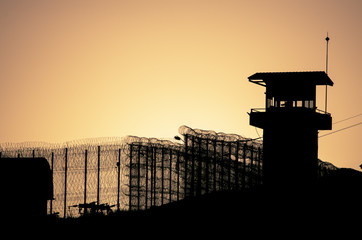 Silhouette of barbed wires and watchtower of prison in Neapolis, Crete, at sunset