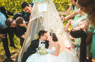 Full length portrait of newlywed couple having fun with bridesmaids and groomsmen in green sunny park. Friends near hand made tent