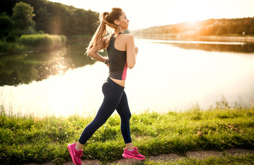 young beautiful woman running by the lake