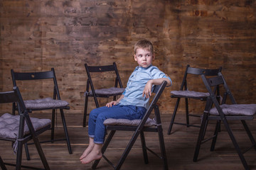 Beautiful and stylish little boy. Portrait of little boy in a stylish blue shirt and blue pants, sitting barefoot on a chair apart from other chairs in Studio on a background of wooden wall