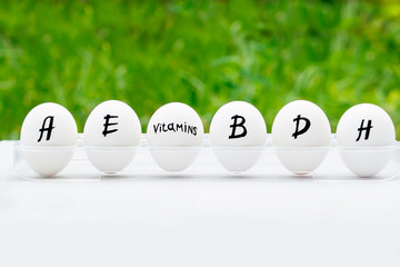 Chicken egg whole in a row with inscription of vitamins, which eggs include