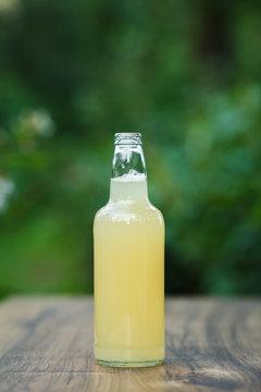 homemade lemonade in glass bottle on bokeh background