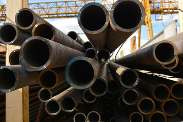 Reinforced tube. Heavy-wall metal pipe. Thick-walled pipe. Stuck of steel pipes. Heavy-gauge pipe bundle in industrial warehouse.