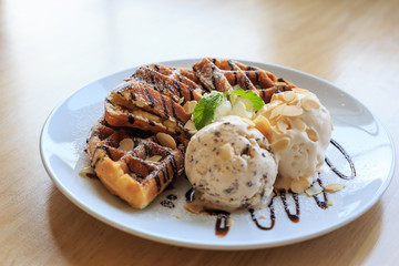 Plate of waffles with ice cream, caramel sauce .