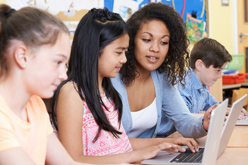 Teacher Helping Group Of Elementary School Children In Computer