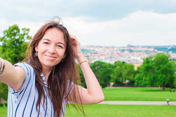 Young caucasian woman making selfie background european old city by mobile phone from the observation place