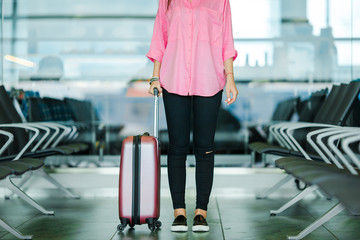 Closeup airplane passenger and pink baggage in an airport lounge waiting for flight aircraft. Young woman in international airport walking with her luggage