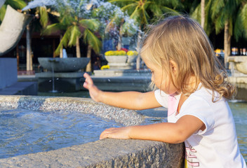 beautiful little girl washing her hands in the fountain