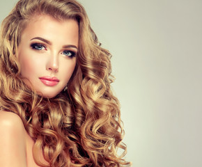 Beautiful girl with long wavy hair . Blonde model with curly hairstyle .
