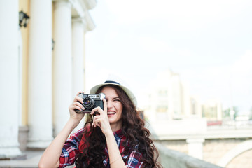 A girl tourist in a hat taking pictures of the urban landscape around the building with columns