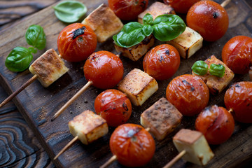 Close-up of skewers with barbecued cheese and cherry tomatoes