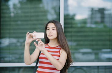 Young Asian woman using smartphone and take a picture.