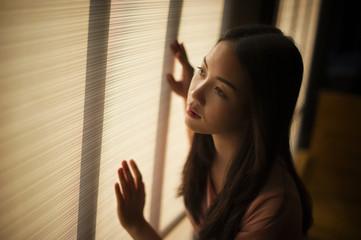 woman standing by the window Feeling sad