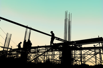Silhouette of construction workers working on scaffolding at a h