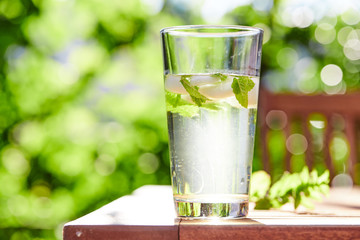 Cool drink with mint and ice on table