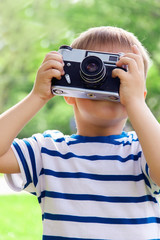 Happy cheerful boy with a camera, the baby photographed outdoors
