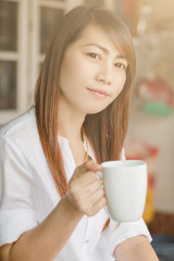 Portrait of young beautiful Asian woman holding white  cup of tea or coffee
