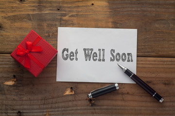 Get Well Soon written on paper with pen,red gift box and wooden background desk.
