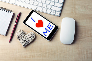 Love yourself concept. Computer peripherals with white wicker heart, notebook and mobile phone on light wooden table