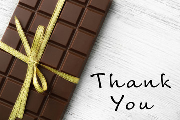 Chocolate bar with bow and text Thank You on wooden background