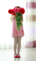 Girl holding fresh peonies bouquet on curtains background