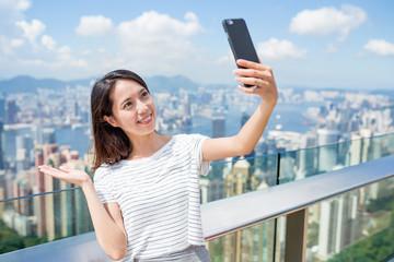 Woman taking selfie by mobile phone in The Peak of Hong Kong