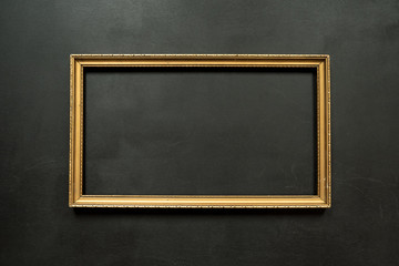 Horizontal gold thin picture frame on the black background with copy space