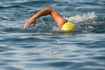 Man swimmer swimming crawl in blue sea,training for triathlon