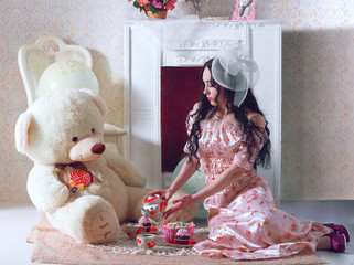 beautiful girl doll is drinking tea with teddy bear