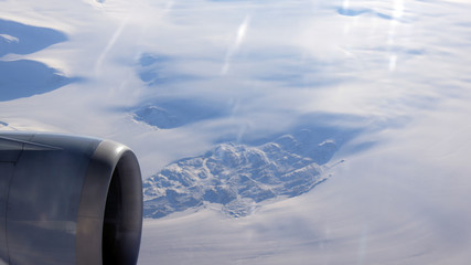 Greenland as seen from the sky, wing view with airplane turbine