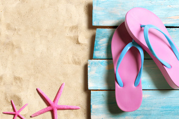 Summer beach accesories and marine life on blue wooden boards on the sand beach