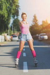 Cheerful teenage girl rolle rskating on the street