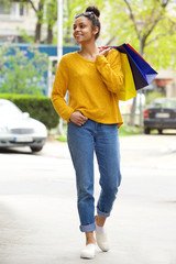Stylish young black lady with shopping bags