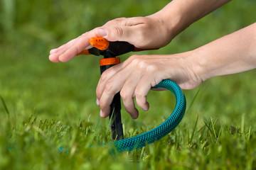 hand of gardener installing sprinkler for irrigation