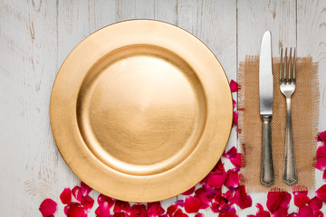 Silverware with an empty tag on a table with an gold plate