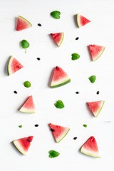 pattern of watermelon slices on wooden white background, top view, flat lay
