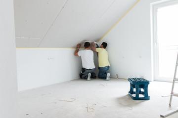 zwei Handwerker schrauben eine Gipskartonplatte fest - Trockenbau