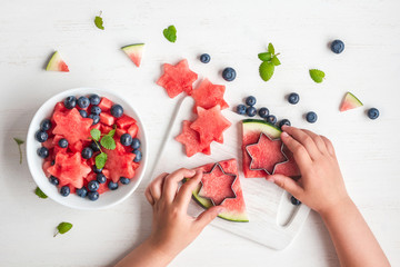 children's hands cooking salad on white table, top view, flat lay