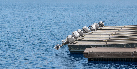 Row of small grey metal boats with outboard motors at rental dock