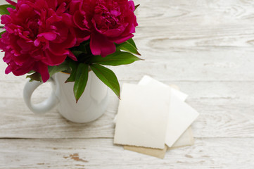 Bouquet of pink peonies in a white jug and old empty photographs close up, top view