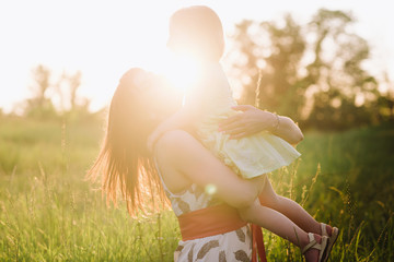 Mom kisses and hugs daughter on nature in sunset light, family, motherhood, child