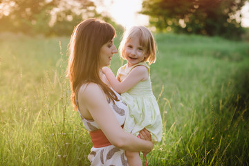 Mom kisses and hugs daughter on nature in sunset light, family, motherhood, child