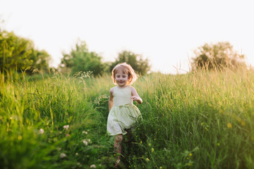 Outdoor portrait of a cute little girl playing in the grass, childhood, happiness, nature, relaxation