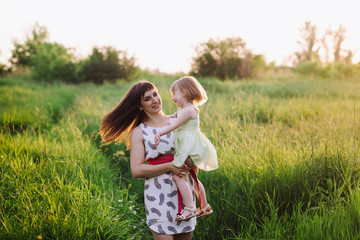 Mom and daughter dancing in nature together in sunset light, the family, motherhood, entertainment, recreation, game