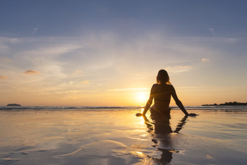 Girl on vacation relaxing on the beach, looking at sunset