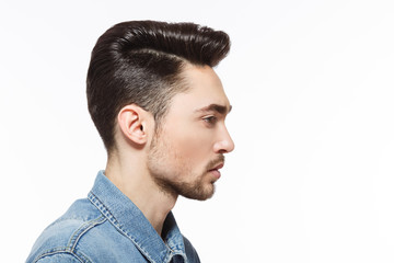 Closeup profile of model man injeans shirt demonstrating his modern hairstyle over white background in studio. Hairdressing concept.