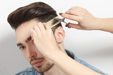 Portrait of handsome man with black hair having haircut in studio. Hairdresser using comb and scissors for creating modern hairstyle.
